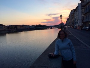 Shirley stands near the Ponte Vecchio at sunset.