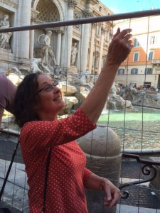 In spite of the fence, Shirley tosses her coin into the Trevi fountain.