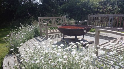 A raised deck at the top of the garden is a place to sit long into the night with the fire blazing.