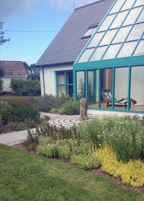 A garden design showing a standing stone, pebble mosaic and colourful planting give a great view from the conservatory in this large family garden..