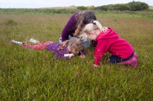 Mother and two young daughters laying down amongst the flowers in a flower meadow