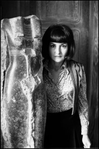 Black-and-white photo of surrealist author Joyce Mansour, next to a sculpture of a headless woman, in Mansour's apartment in Paris.