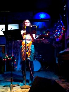 Shanna Compton reading at Stain Bar in Brooklyn. She is wearing a yellow dress and holding a book, under a blue spotlight.