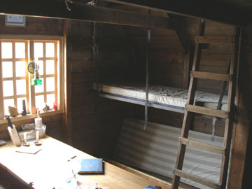 """This is the interior of the hut, or at least as much as I could fit into a camera frame with my back against the opposite wall. The guest book on the table had an entry from a Canadian hiker who wrote, """"Time spent in the mountains is never deducted from the rest of your life."""""""