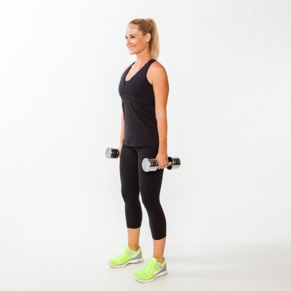 Stand with feet hip-width apart, holding dumbbells by sides.