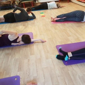 People lying on the floor on mats doing Pilates side leg exercises stretching