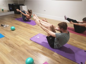 People sitting on mat performing Pilates in corporate class