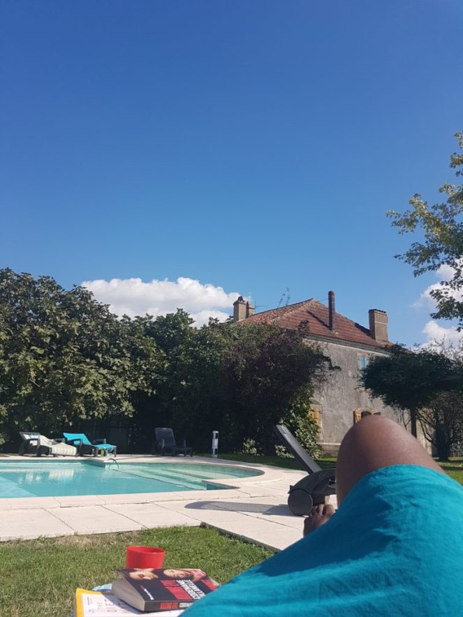 View of blue sky, old building roof and ladies knee near pool