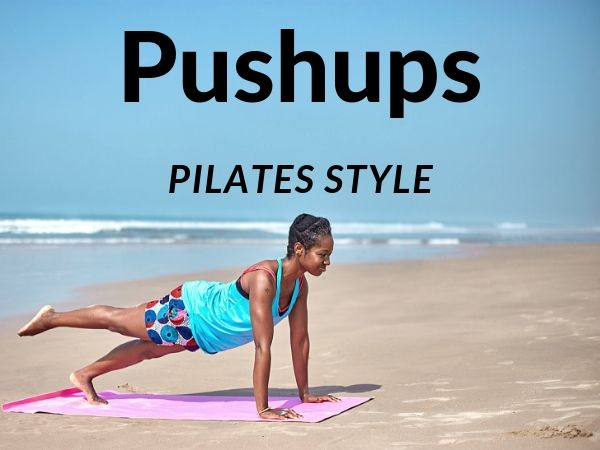 Woman on a beach doing a push up with one leg extended behind her.