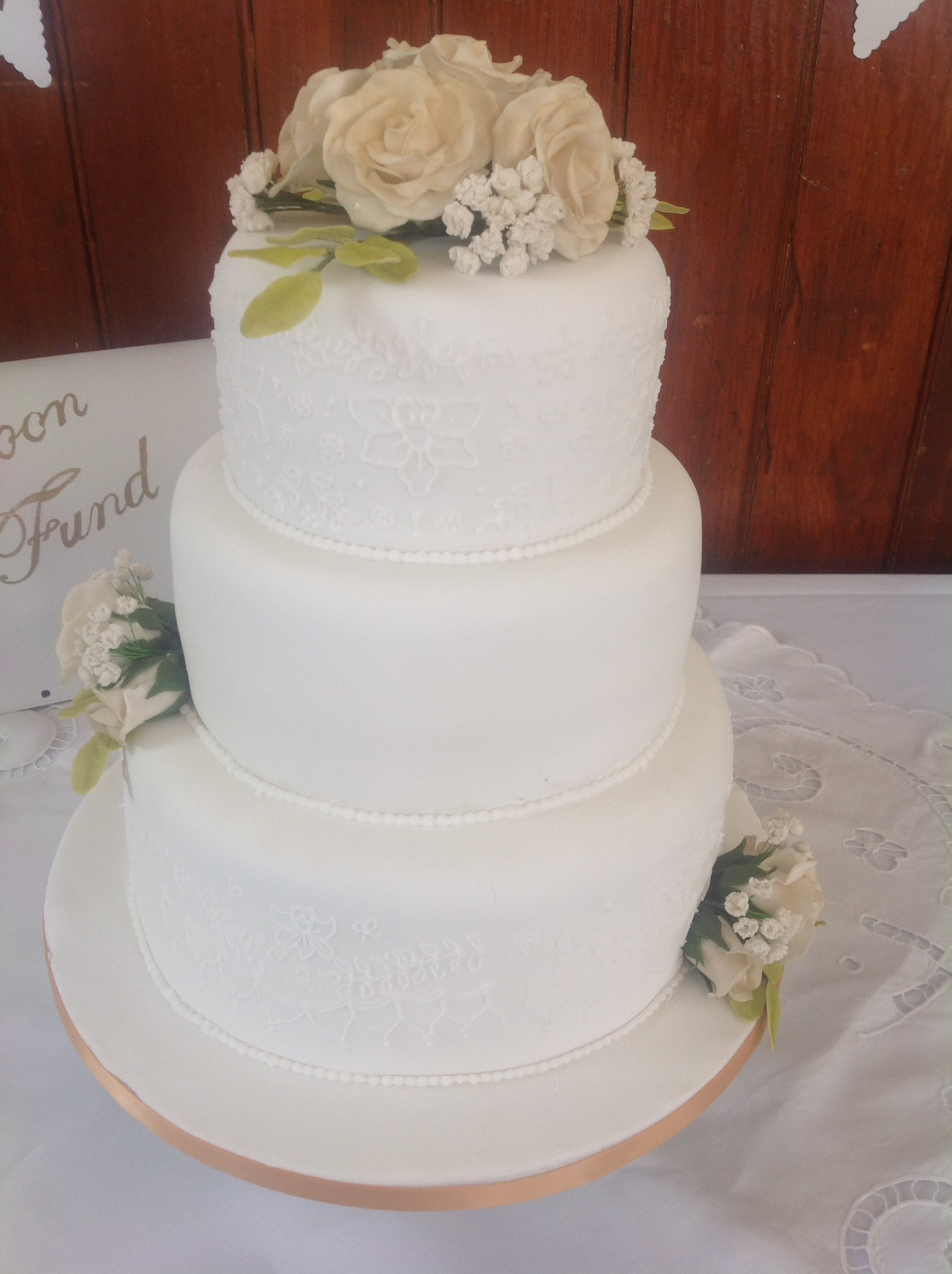 a 3 tired stacked cake in white with lace detail piped on bottom and top tier with a posy of roses, gip and leaves