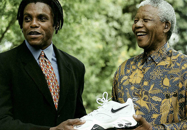 971208SH05: SAFRICA  : PERSONALITIES : ATHLETICS : 6DEC1997 - President Nelson Mandela and Carl Lewis (multi Olympic gold medalist) presents Nike shoes to the President, at the  president's lower Hougton home in Johannesburg.(Photo by Shaun Harris / www.afrikamoves.co.za)