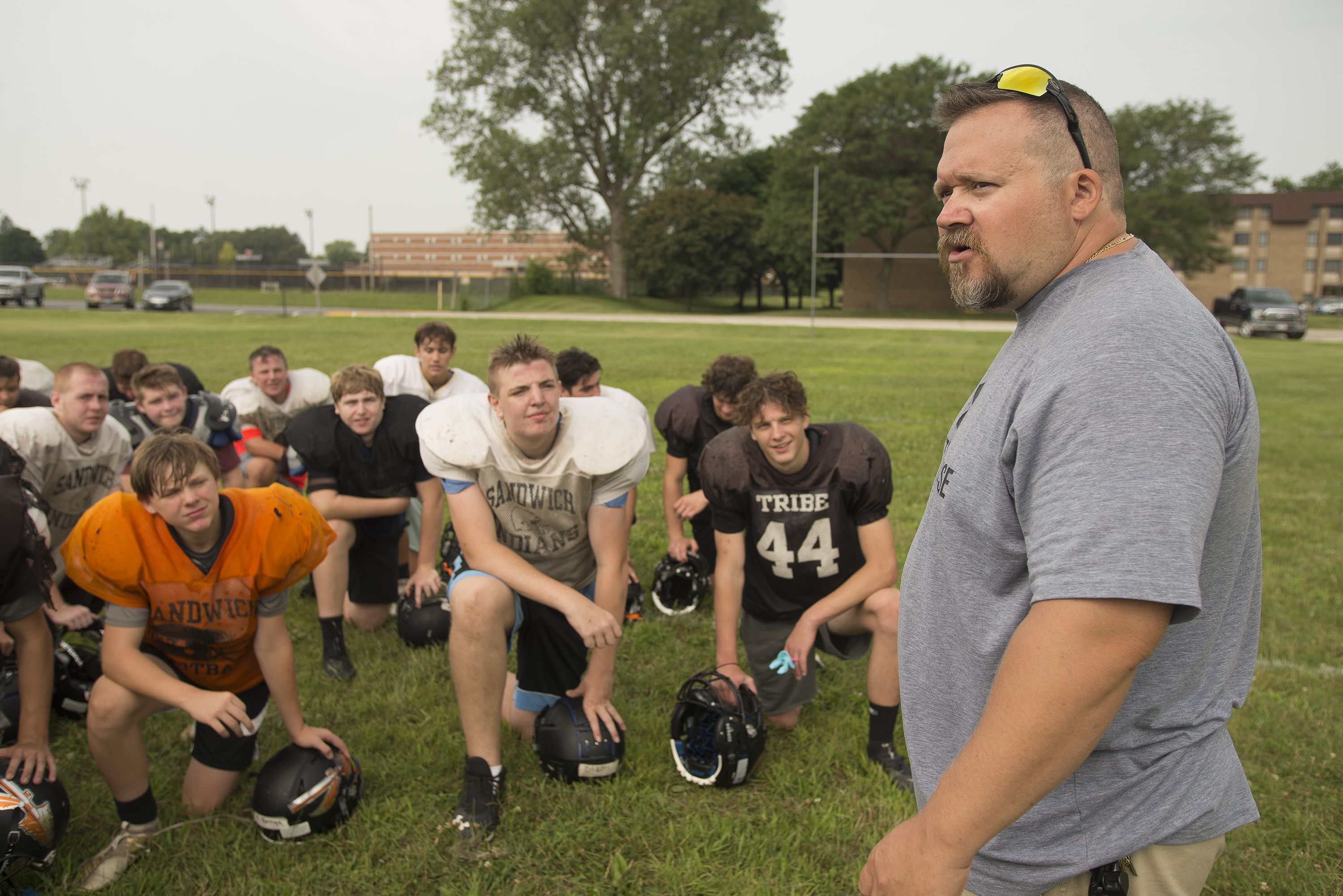Head coach Kris Cassie talks to his team after a session of summer football camp at Sandwich High School.