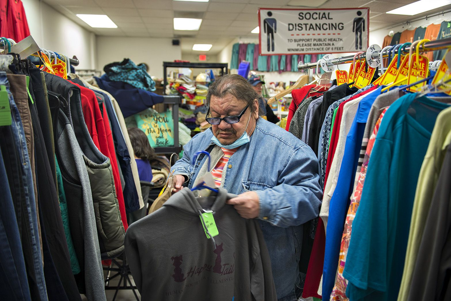 Manny Campos looks over clothing at Happy Tails thrift shop. Tuesday. Many local businesses, organizations and people have stepped in to help the 70 or so displaced residents.