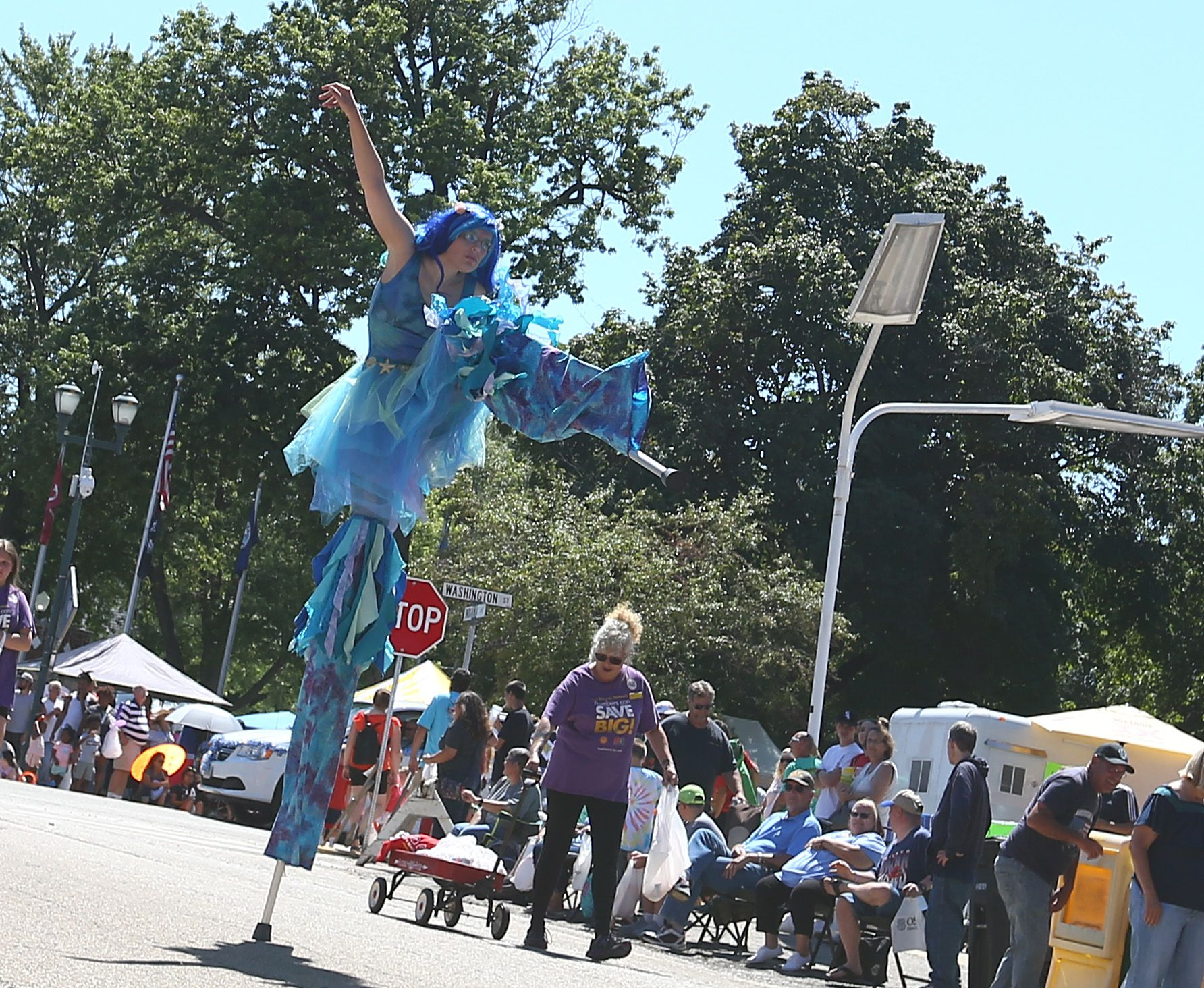 A woman stands on one stilt during the during the 74th annual Sweet Corn Festival Parade in Mendota on Sunday, Aug. 15, 2021.