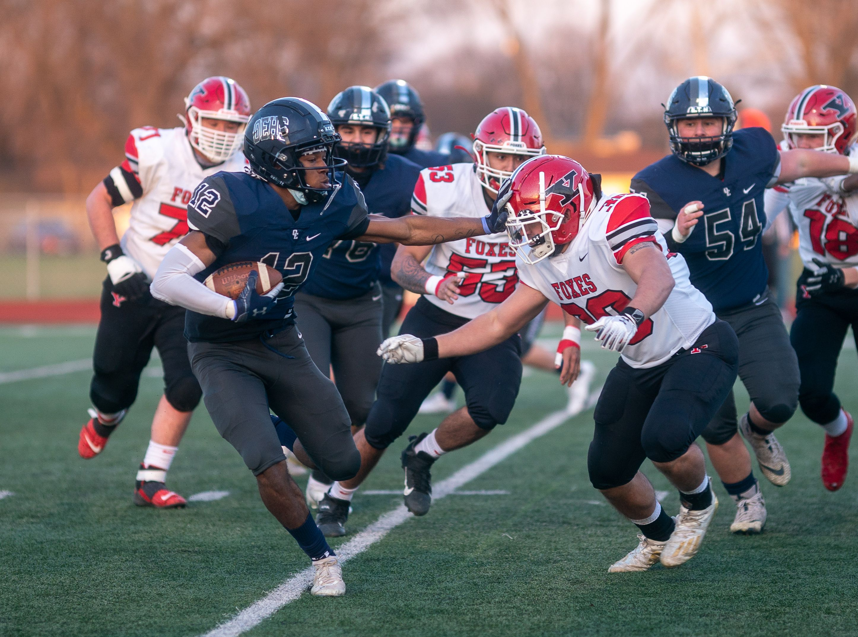 Oswego East's Darquel Sanders (12) carries the ball against Yorkville's Christian Aquino (30) during a football game in Aurora April 2