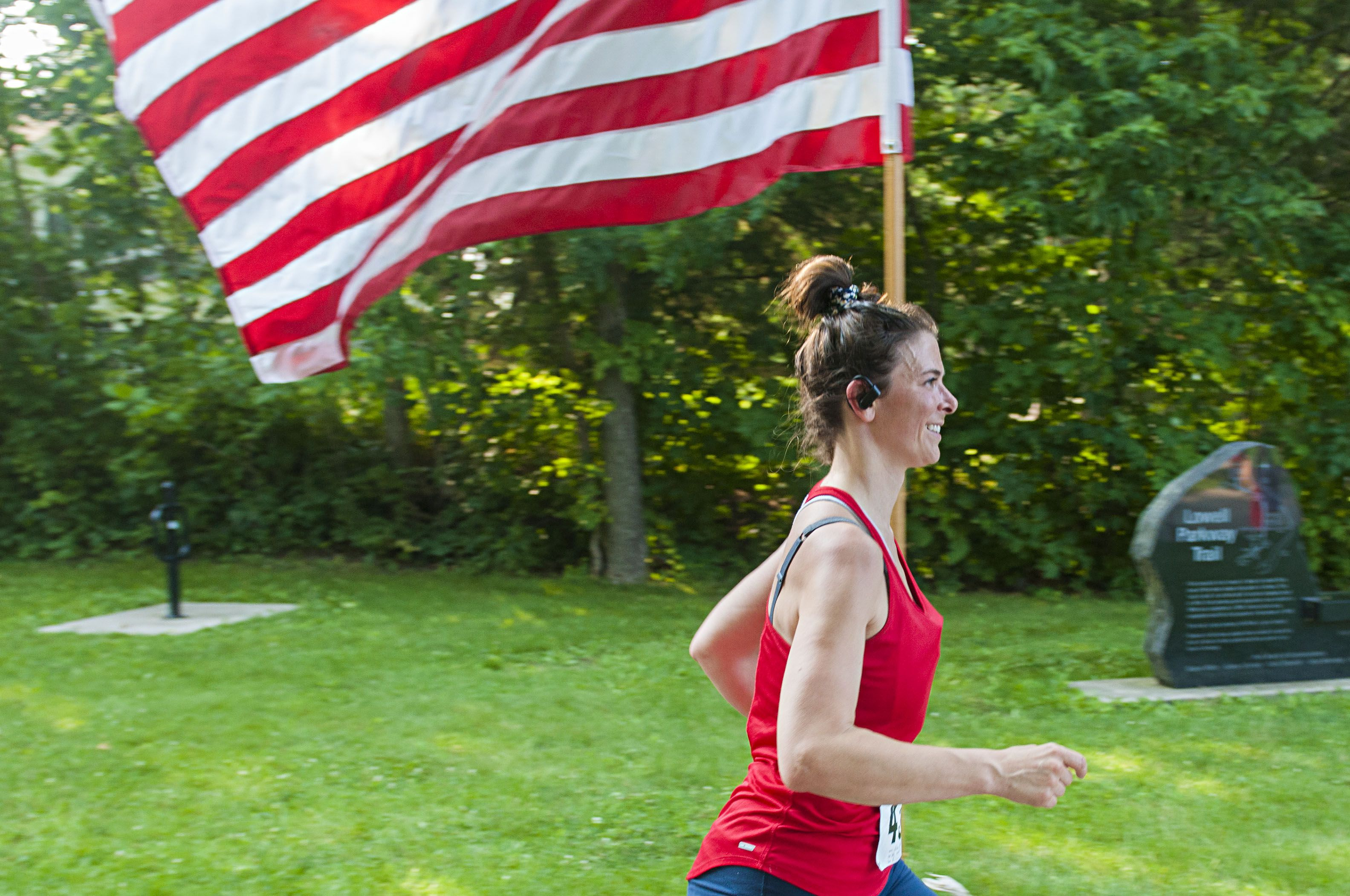 Elise Ulferts-Hume zips by a flag after completing the Reagan Run.