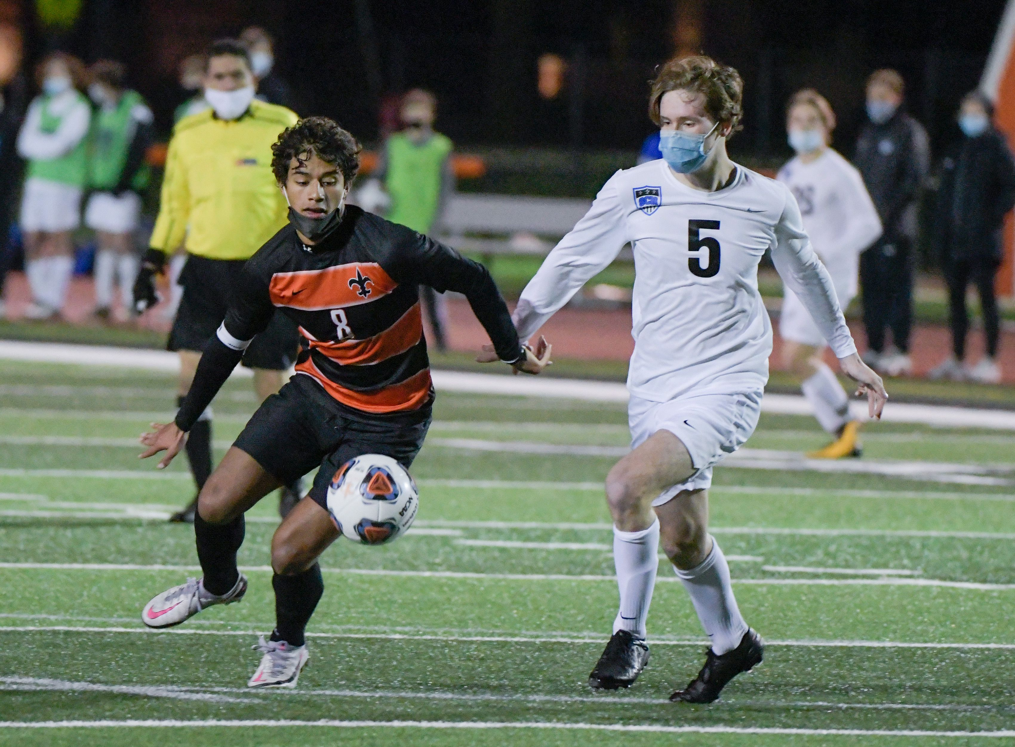 St. Charles East's Sebastian Carranza (8) and St. Charles North's Michael DePasquale (5) battle for control of the ball during the second half of varsity boys soccer in St. Charles Apr. 8.