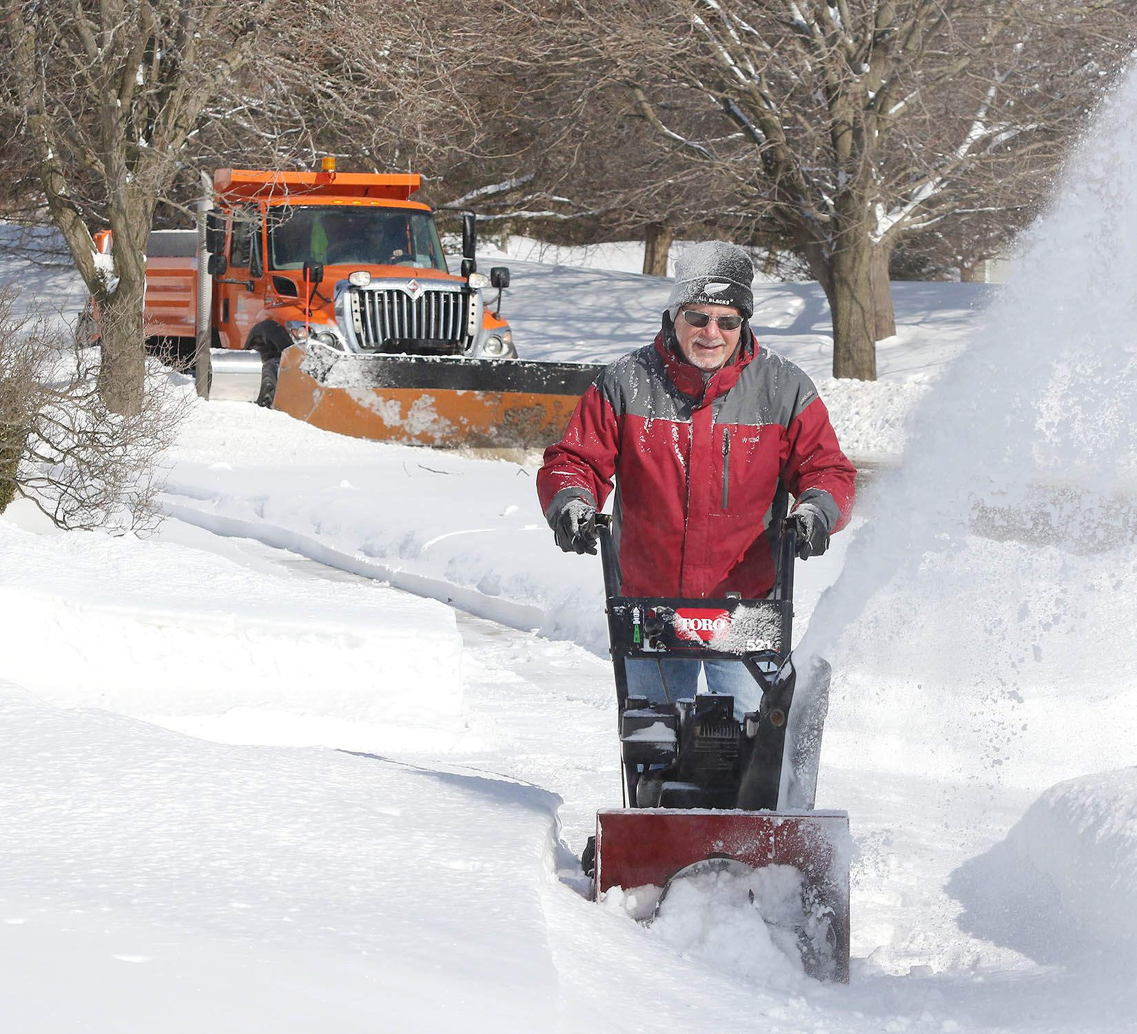Bill Syversen uses a snowblower on the sidewalk in front of his house as a City of DeKalb snow plow does the street Tuesday morning. More snow fell Monday night adding to the several inches already on the ground.