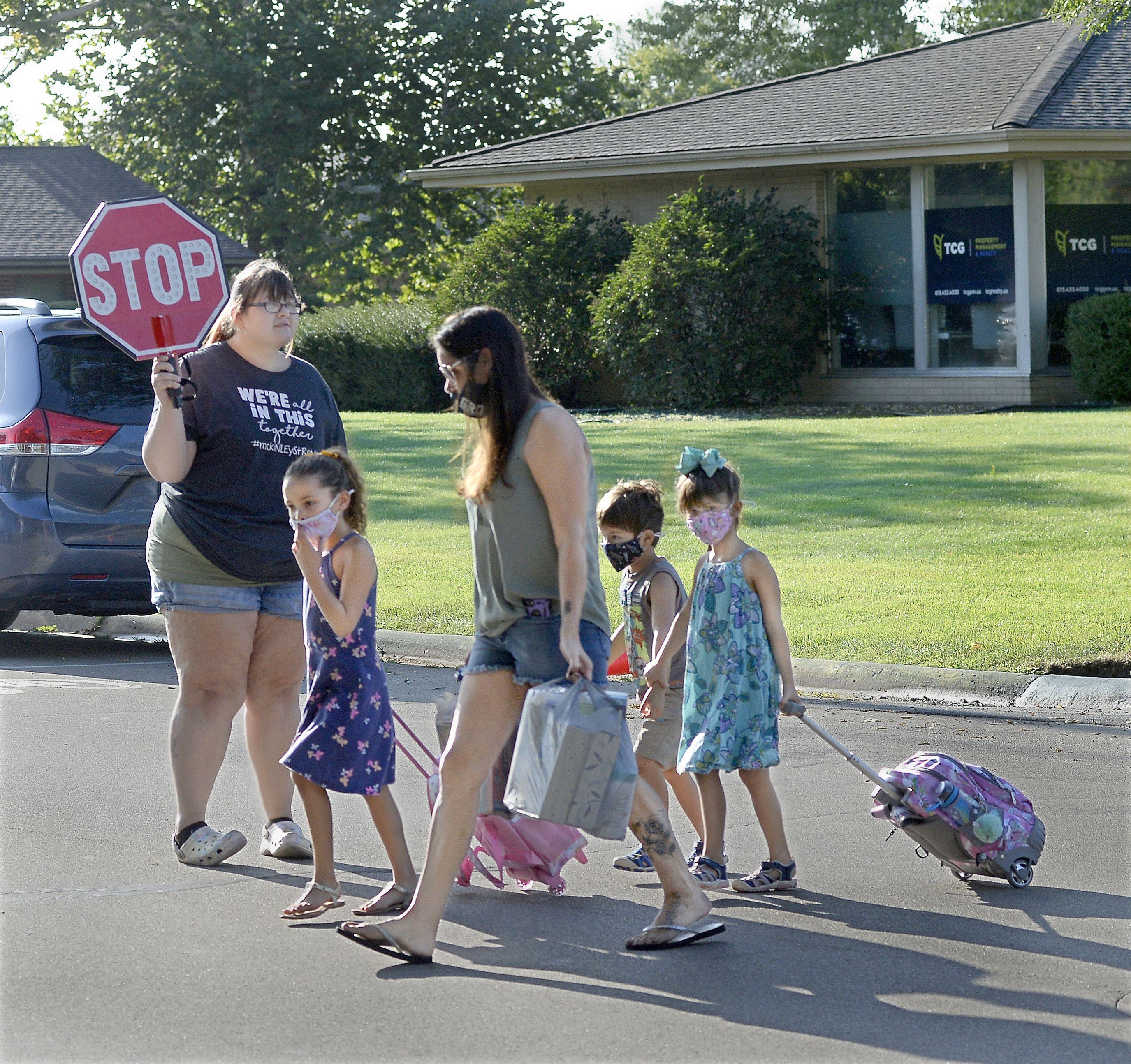 Parents walking their children Wednesday, Aug. 25, 2021, to McKinley School in Ottawa cross McKinley Road as all schools in the Ottawa Elementary District began the new school year.
