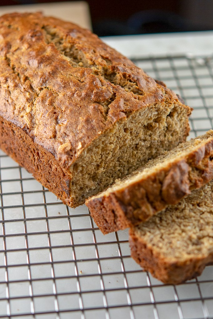 banana oat bread loaf sliced on a wire rack