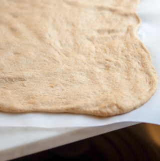 un-baked white whole wheat pizza dough on a baking sheet lined with parchment