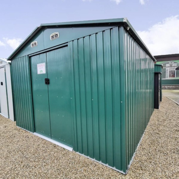 The Colossus Steel Shed in green on the grounds of the Sheds Direct iRELAND SHOWRROM IN NORTH DUBLIN. The base is a golden brown and the sky is bright blue. The shed is sturdy looking, the doors are closed and there is a pricelist stuck to the door.