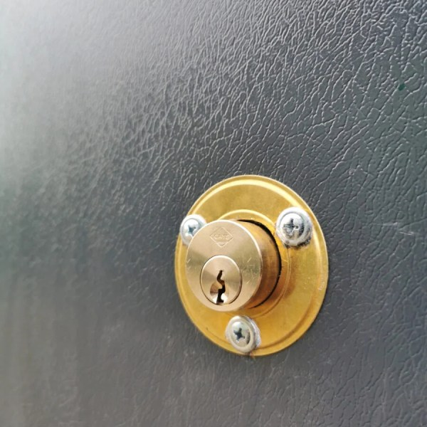 The new built in keylock on the PVC Cladded sheds from Sheds Direct Ireland in Dublin. The lock itself is circular and gold and it protrudes from the door by about one inch. There is a circular mount around it that is also gold and three screws attach this to the wall.
