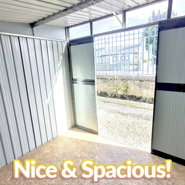 An internal view of the steel pent shed. The ply floor is gold and draped in sunlight coming in through the open double doors and window. The walls are vertically rivited and they are a pale grey.