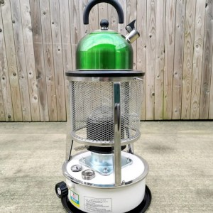The camping stove from Sheds Direct Ireland. It's got a white body with a black base and a black dial. There is a mesh grate with the heating element underneath. A luminous green kettle is sitting on top, though the sign below reads 'kettle not included'