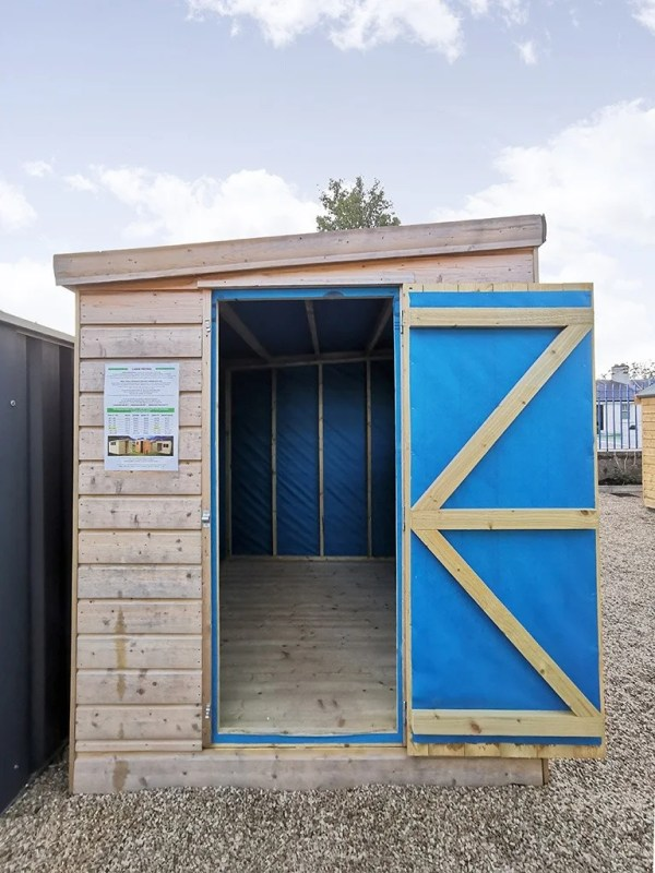 The door is open in this photo. The internal blue lining is visible. This lining has wooden slats and joists over it for support to the shed.