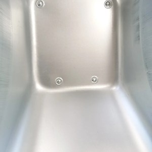 The internal detail of the barrow on the steel wheelbarrow. It's polished steel with 5 covered rivits visible.