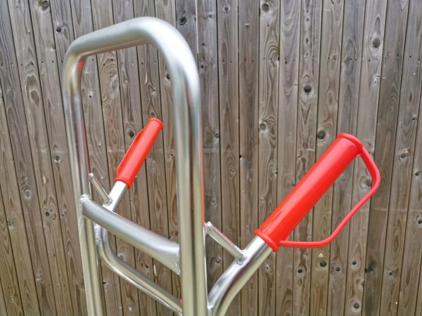 The tall back and handles of the aluminium sack truck. The body is silver, but the handles are bright red. They have looped 'knuckle guards' too