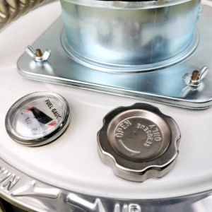 The fuel gauge and fuel entry point for the camping heater stove. The cap for refuelling is silver and matte and gauge is a half-bubble with a triangular fuel gauge image. It's red at both ends and a thin arrows shows the fuel level