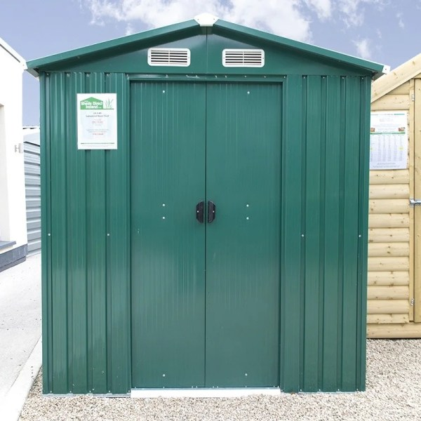 The 6ft x 8 ft Steel shed on the Sheds Direct Ireland showroom in Finglas. It's a green shed, with vertical steel sheets and white vents above the door. There is a wooden shed to the right and a block build unit to the left. The doors are closed and the black handles are visible.