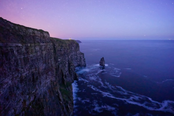 The Cliffs of Moher in Clare, Ireland just after dusk. The sky is purple, almost pink and the waves are slowly crashing against the rocks deep down below. It is very serene.