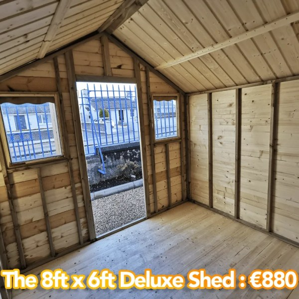 8x8 Deluxe Shed Shed as seen from inside. It has two windows either side of the door and a wooden floor, roof and walls.