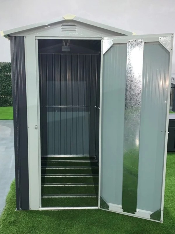 The 4x6 storage unit on a lawn, against a grey sky. The unit's door is open and the metal door truss bar is reflecting the camera's flash. The Internal floor frame is visible and the grass that it sits on is poking through these bars.