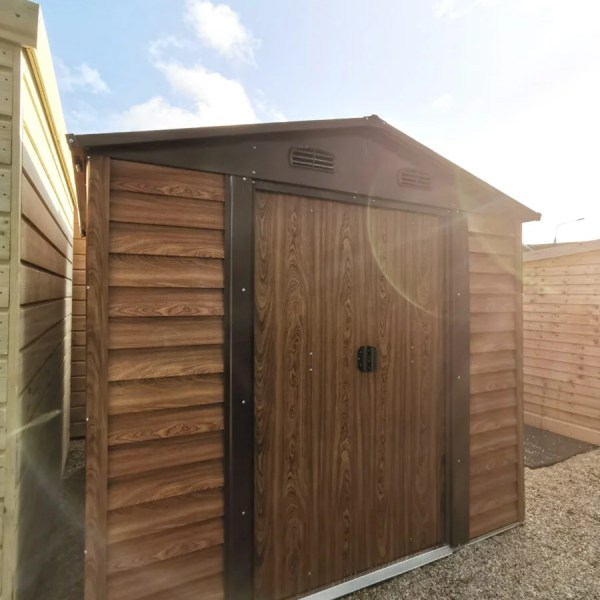 Woodgrain Metal Sheds in our Finglas Showroom. They are brown and have a faux-woodline appearance. They are standing on a concrete ground and the sun is setting behind them to the righ,creating a golden sky and a camera-lens flare onto one of the sheds