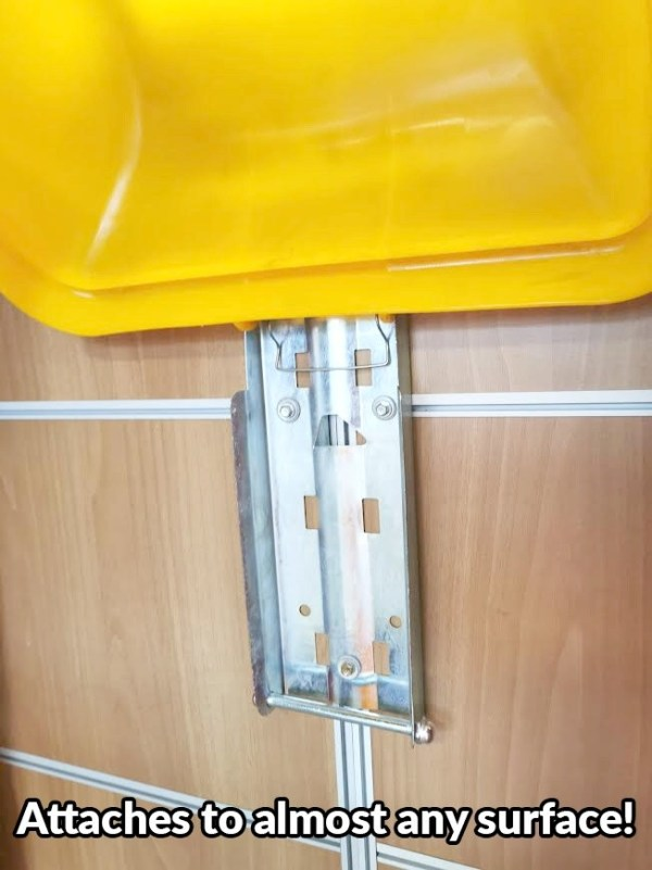 The shiny, metal mounting plate of the Covid Waste Bin. It's a greyed steel with 6 port holes at the back. The lid of the bin is in place, but the body is not. It's attached to a wooden surface.