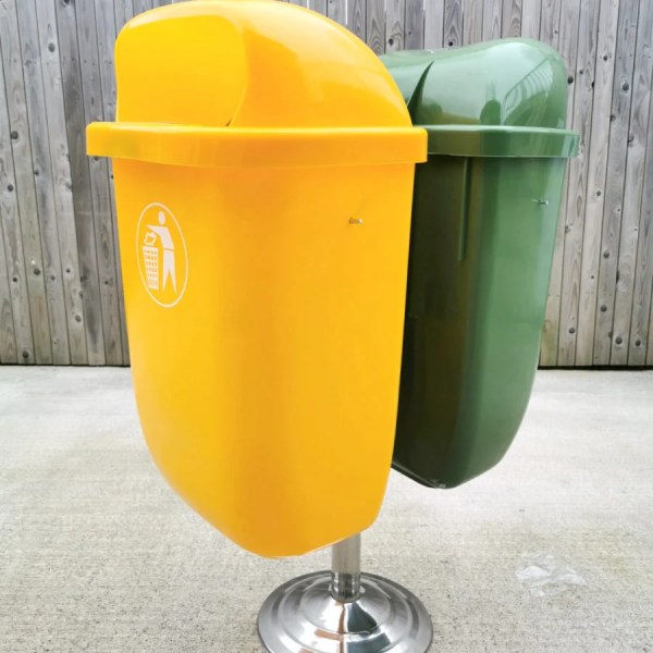 The yellow bin in front of the green bin on the silver stand