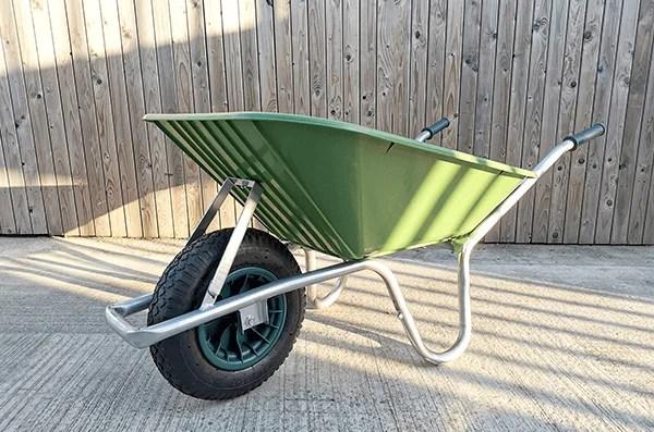 A green plastic wheelbarrow