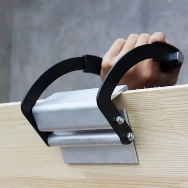 The panel gripper in use holding a piece of wooden board. The grip is to this side of the camera and the person holding it is on the other.