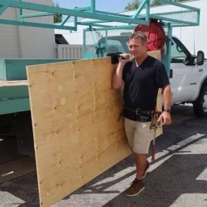 A man carrying a large plywood board using the panel carrier. He is holding it at shoulder height and has unloaded it off the side of a white truck beside him.