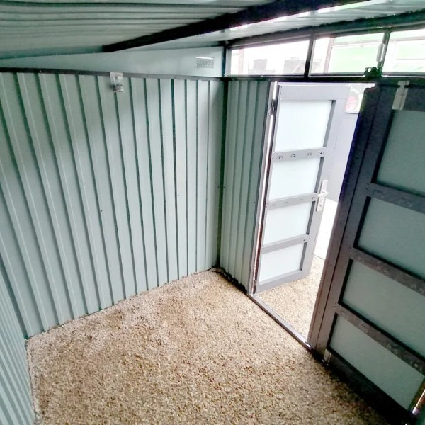 Inside the Premium Pitched Steel Garden Shed. It has no floor and the pebblestones are visible as the base. The door is open and light pours in through it and also from the large window above the door