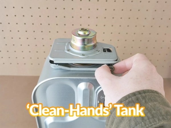 The clean-hands tank of the minimax heater in use. A hand is pulling the pin to open it.
