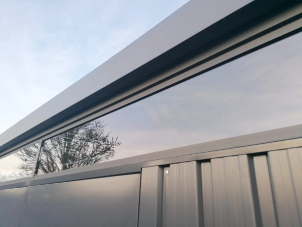 The large polycarbonate windows on the premium panoramic shed, seen up close and reflecting the sky behind the person taking the photograph