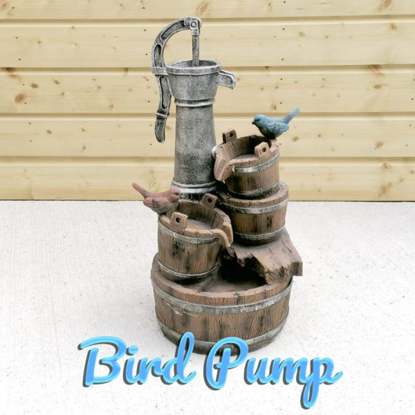 The Bird Pump Water feature against a wooden shed. It is a large enough sized water feature with three buckets and two birds, one red, one blue - on it.