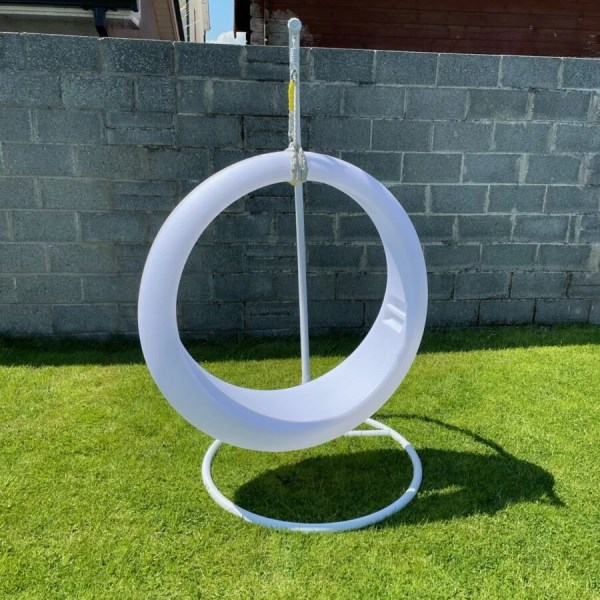 The LED Swing chair in a garden in Dublin, Ireland with the lights off. The chair is bright white and circular with a thicker bottom than top. The grass is bright green below and there is a grey stone wall behind