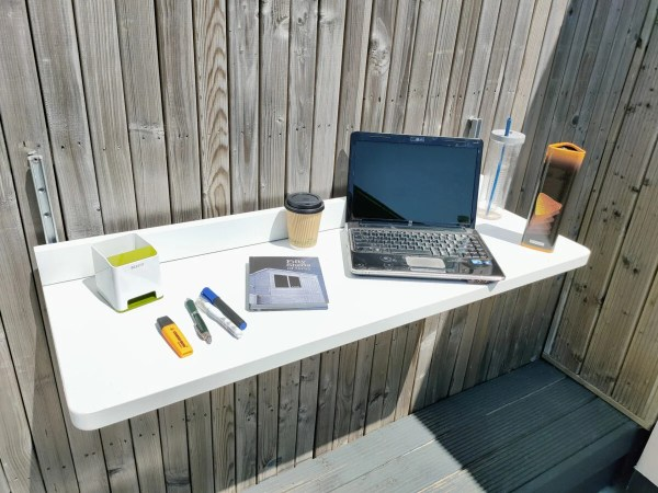 The Balcony Table filled with items including a laptop, a large book, a box of crisps, pens, a stationary holder, a coffee cup and pens.