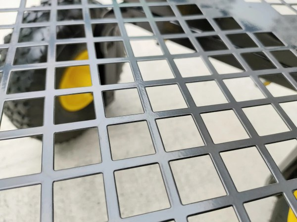 The detail of the mesh at the bottom of the mesh cart. It is a semi-matte painted black steel and the wheels are visible through the mesh.